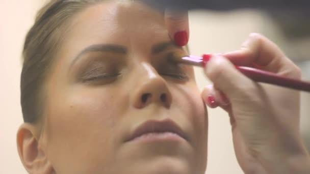 maskérka maluje dívčiny oči