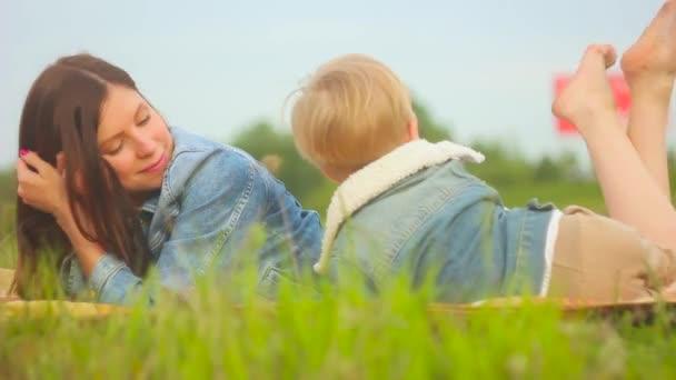 Matka a dítě sedí na trávě
