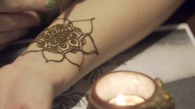 A mester mehendi felhívja a lány kezét. Gyönyörű mintákat a henna. Virágok henna a kezét. A kezét a szép vonalak rajzolása