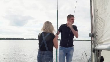 Young couple ride the yacht. The girl with the guy in jeans clothes walk on the yacht by sea.
