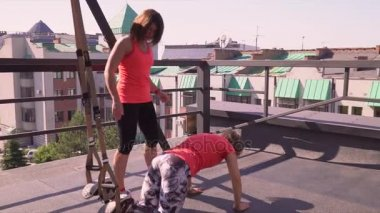 Girl doing lunges with dumbbells. The girl does attacks in the gym on a street terassa