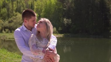 Lovely couple embrace on the bank of the lake and embrace. Beautiful the guy with the girl stand in an embrace on the skoyena. The guy embraces the girl in a garden. Beautiful couple stand at the lake