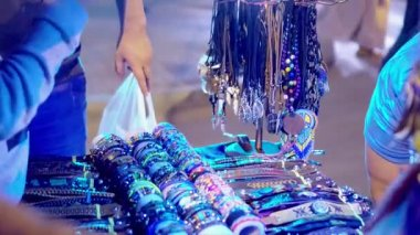 People watch fair counters with jewelry in the night city. People in the light of blue lamps watch bracelets
