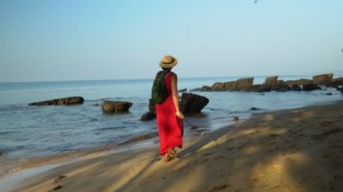 The woman in a straw hat walks along the beach. Sunny day on Phu Quoc Island. Beautiful open spaces of the ocean