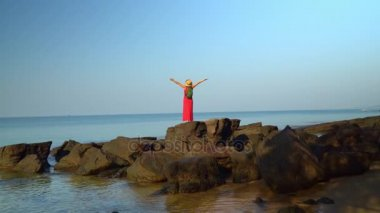 The woman in red in a dress with a backpack costs having straightened hands on big black stones at the coast of the island. The woman looks in a distance.