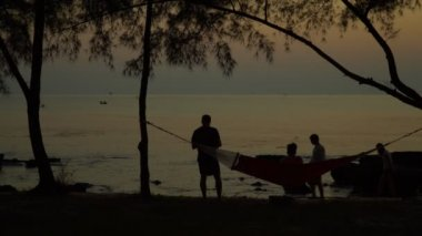 The man and the woman photograph a beautiful decline on the ocean horizon. Smiling people stand on the coast of the tropical island. Vietnam. The woman at a hammock on the ocean coast