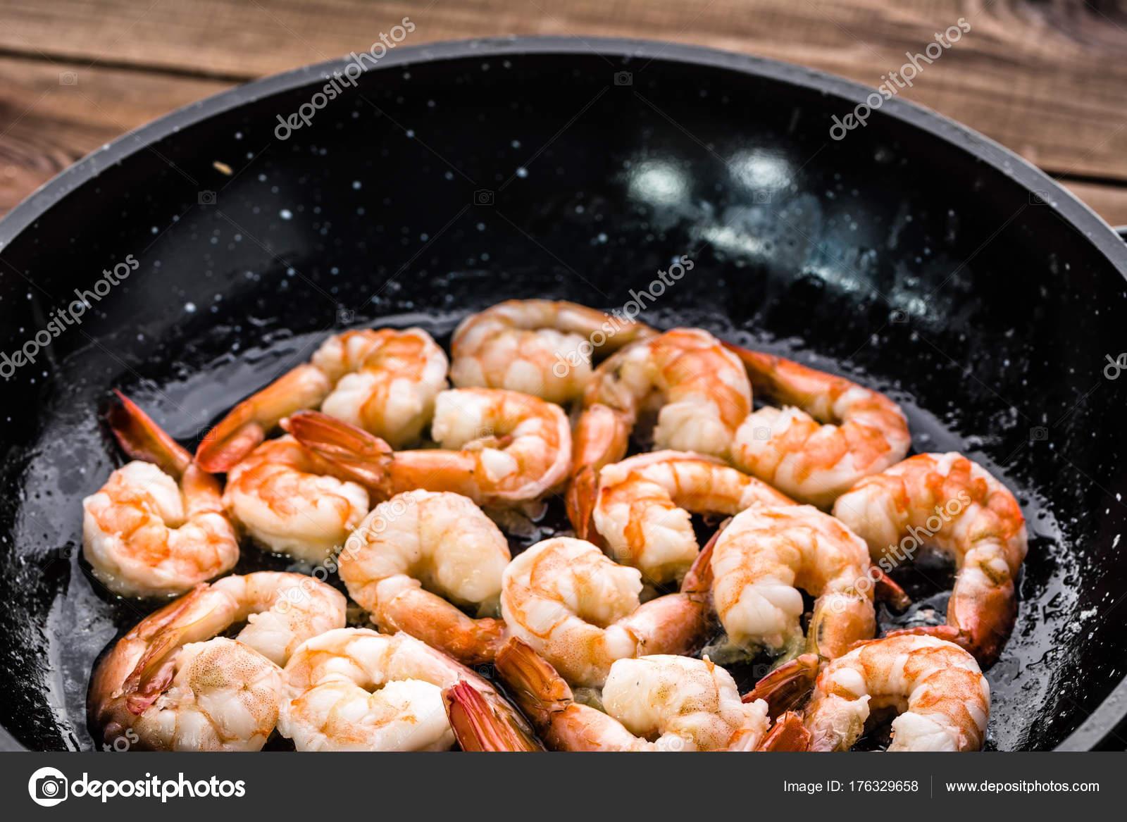 Свежие рыбы, креветки с травами, специи и овощи на темной.