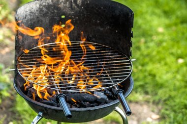 Barbecue grill with fire, charcoal and grid for grilling in the garden, summer picnic on grass, outdoors