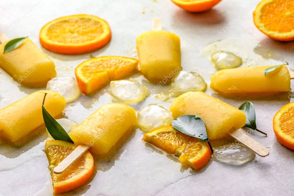 Orange popsicles with frozen juice and ice cubes, summer refreshing snack