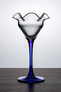 Empty cocktail glass with blue thin and high leg on dark wooden surface in white backlight