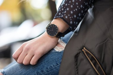 fall fashion outfit details. young businesswoman in elegant trendy clothing with accessories on hands. beautiful black and golden elegant watch.