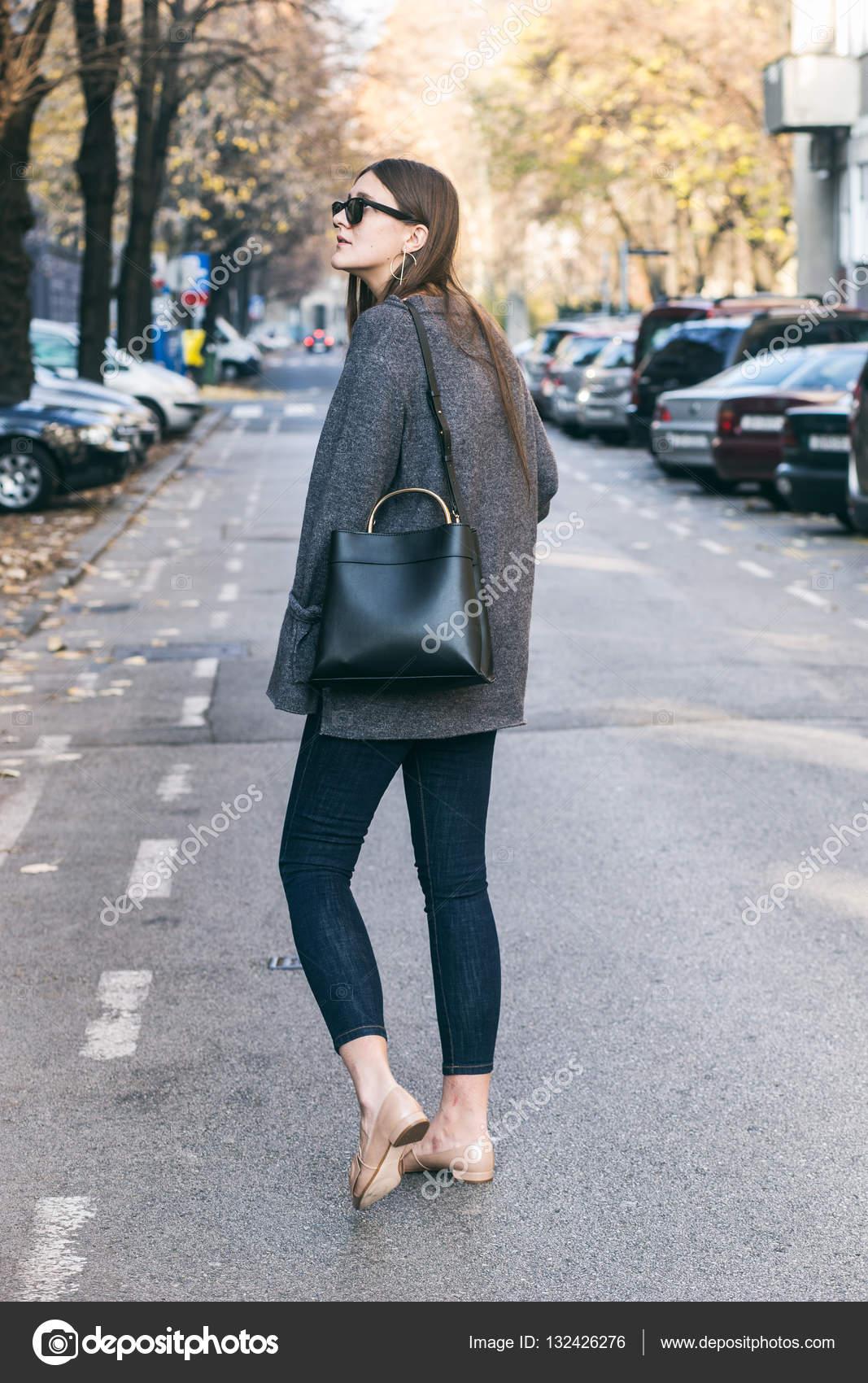 fe07132fc Blogueiro de moda morena linda posando na rua. uma camisola à moda outono  roupa,
