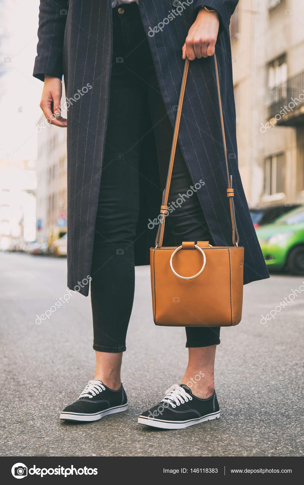 a53145edc detalhes de roupa moda blogger. mulher elegante vestindo um casaco azul de  grandes dimensões, calça jeans preta, tênis pretos uma bolsa marrom na  moda. ...