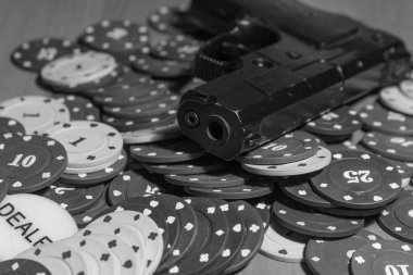 Pistols and poker chips in black and white on the game table