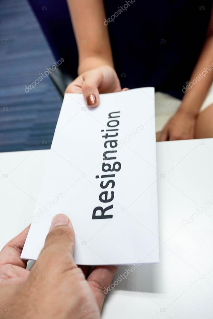 close up submitting a resignation letter to the boss stock photo