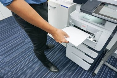 A man is printing document  and copy a document