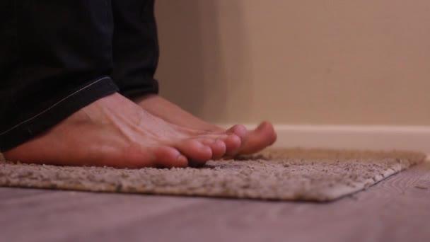 Fungo del piede. un uomo graffia i piedi, in piedi a piedi nudi sulla moquette. Prurito intenso dei piedi