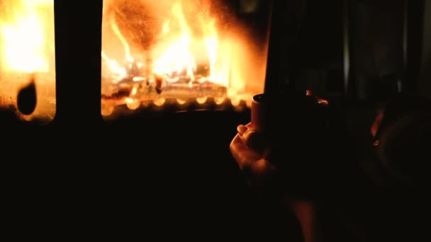 Close up of man drinking coffee or tea in front of a fireplace. girl holding cup of cofee or tea with bonfire on background