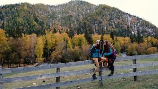 Portrét zábavy dívky při hloupé a skvělá selfie společně s krásných zasněžených hor v pozadí. Dvě kamarádky pomocí smartphone pro autoportrét