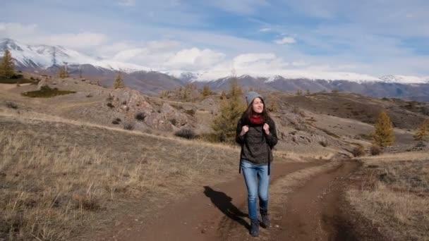 Tramp žena chůzi s batohem obdivovat zasněžené krajiny mountain view. krásné turistické na trek těší venkovní aktivní životní styl v krásné přírodě. Slow motion záběry