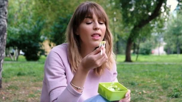 Portrét mladé krásné dívky jíst vegetariánský salát. Studentka si oběd v parku. Úbytek na váze. Vegetariánské jídlo. Zdravé stravování a dietní koncepce