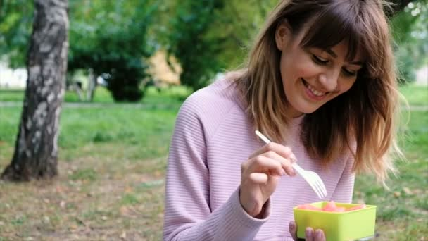 Portrét mladé krásné dámy jíst meloun. Zdravá usměvavá dospívající dívka s mísou salátu a vidlice. Úbytek na váze. Vegetariánské jídlo