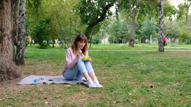 Zdravého životního stylu dívku jíst salát, usmíval se šťastný venku na krásný den. Zdravá usměvavá dospívající dívka s mísou salátu. Připravit a sekání zeleně pro veganské. Zdravé stravování a dietní koncepce