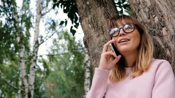 schöne emotionale junge Mädchen spricht Handy und lächelt. Hipster junge Frau benutzt Smartphone im Park.