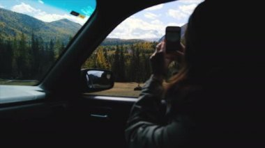 Back view of young woman sitting in the car and taking photo with smartphone during road trip. Amazing snowy mountains view from car window. 4k footage