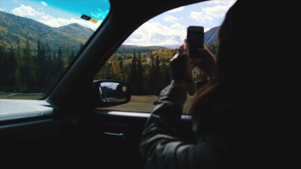 Rückansicht des junge Frau sitzt im Auto und nehmen Foto mit Smartphone während der Fahrt. Traneler genießen Sie erstaunliche schneebedeckten Bergen Ausblick vom Autofenster. 4 k Filmmaterial. sonnigen Herbsttag