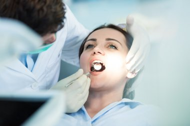 Dentist examining Patient teeth with a Mouth Mirror.