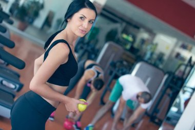 female holding apple in gym