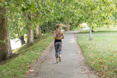 Woman running in park on beautiful summer day.