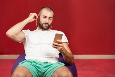 man sitting on a gym ball holding a phone