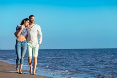 Happy interracial couple walking on beach.