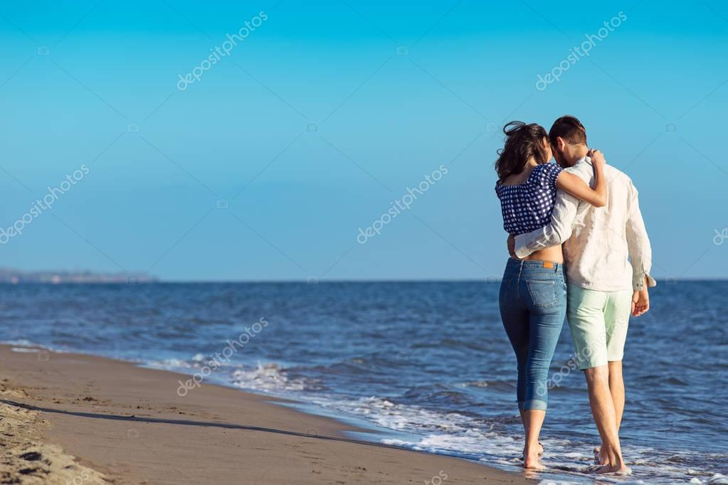 Happy interracial couple walking on beach.