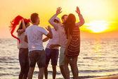 Mladí lidé tančí na pláži