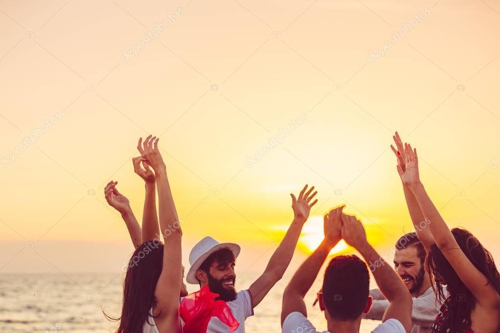 people dancing at the beach with hands up.