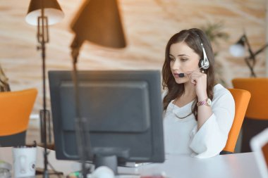 Attractive woman listening to music while working in startup business office