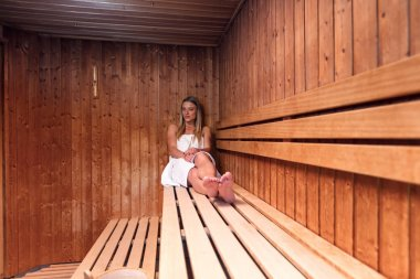Beautiful blonde young woman relaxing a sauna