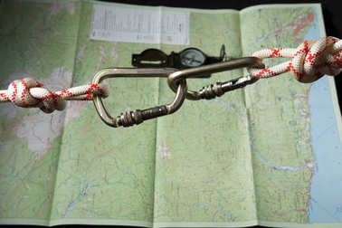 two large steel carabiner for mountaineering with a white and red rope is coupled on the background of a topographic map with compass