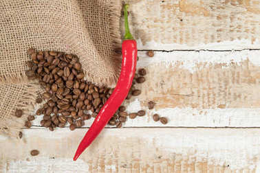 coffee beans in a bag scattered on a wooden background with hot red pepper