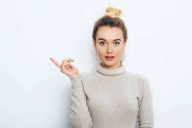 Look There! Surprised Attractive young female lady wearing in sweater with hair bun showing emotions on white wall. Shocked woman points with forefinger at copy space on white background. Amazement