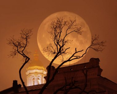 Supermoon with a church and a tree in foggy weather