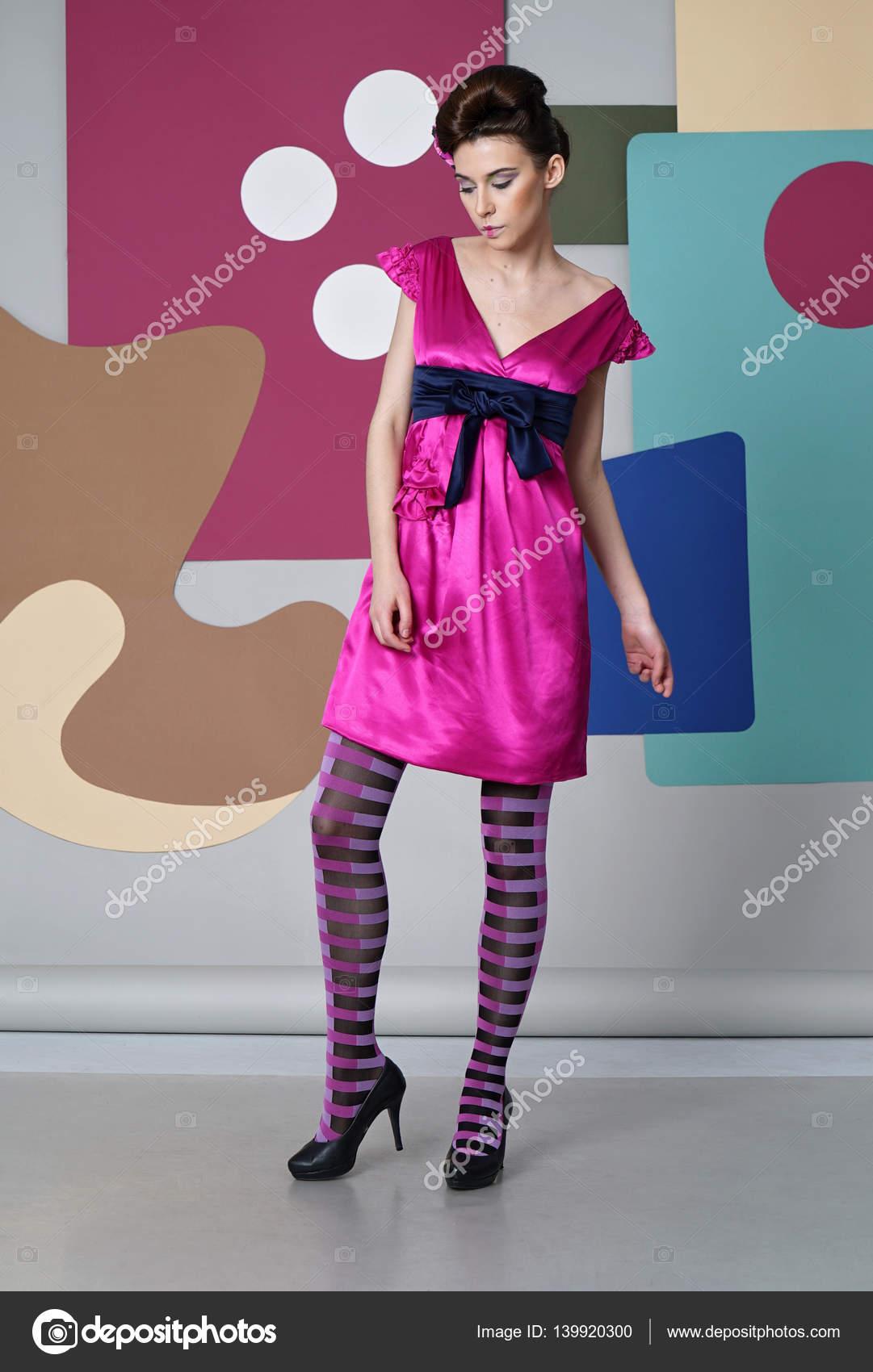 Mujer joven en vestido rosa con un corte profundo se mueve en el ...
