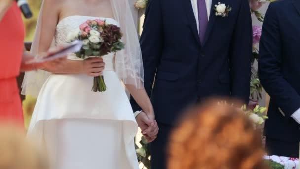 Coppie che tengono le mani vicino a arco di cerimonia nuziale
