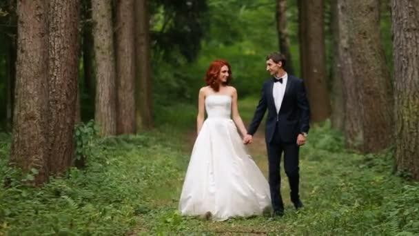 Nevěsta a ženich, drželi se za ruce jdou lesem