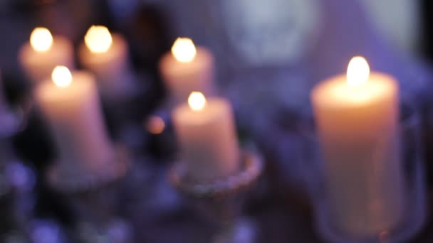 burning candles in candlesticks on the table