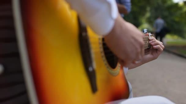 junger Musiker spielt Solo auf klassischer Gitarre, Fingerstil aus nächster Nähe. Eine Akustikgitarre verwendet ausschließlich akustische Mittel, um die Schwingungsenergie der Saiten in die Luft zu übertragen, um einen Klang zu erzeugen