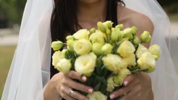 Portréja egy menyasszony, esküvői ruha, virág egy napos park.